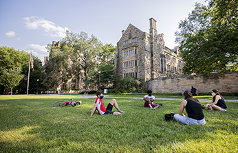 Students sitting outside on grass in a circle physical distancing